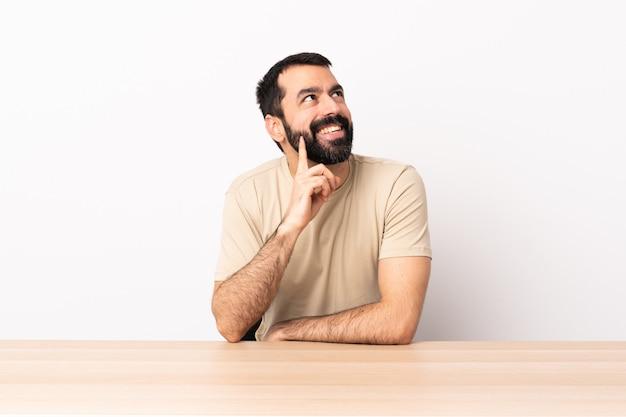 Uomo caucasico con la barba in una tabella che pensa un'idea mentre guardando su