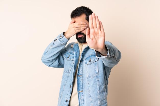 Uomo caucasico con la barba sopra il gesto di arresto e la copertura isolati di fabbricazione