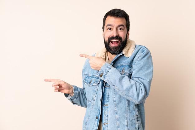 Uomo caucasico con la barba sopra il lato sorpreso e indicante isolato