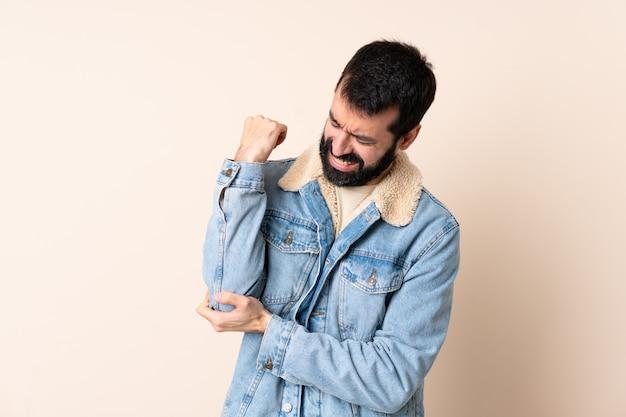 Uomo caucasico con la barba sopra isolato con dolore al gomito