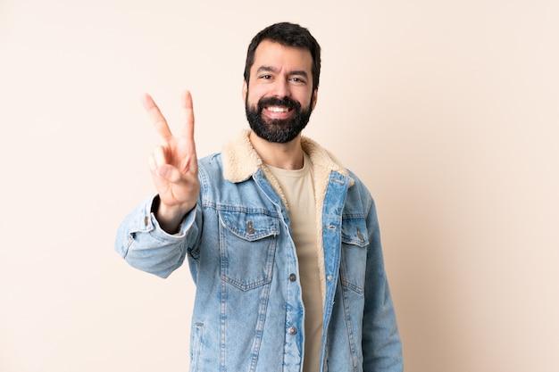 Uomo caucasico con la barba sopra isolato sorridente e mostrando il segno della vittoria