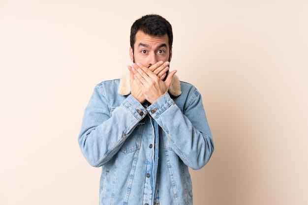 Uomo caucasico con la barba sopra la bocca di copertura isolata con le mani