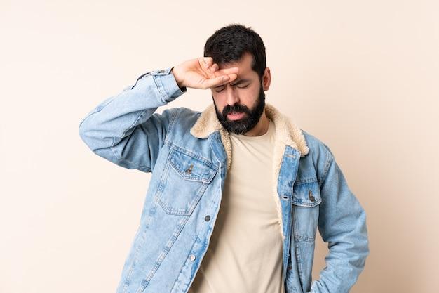 Uomo caucasico con la barba sul muro con espressione stanca e malata