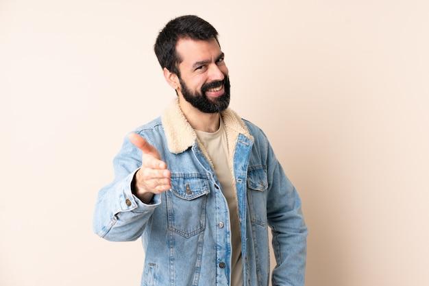 Uomo caucasico con la barba sulle mani stringere isolate per chiudere molto