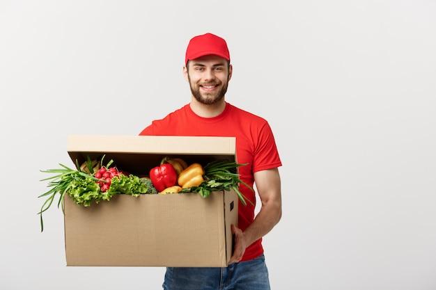 Uomo caucasico del corriere di consegna della drogheria in uniforme rossa con la scatola di drogheria con frutta fresca