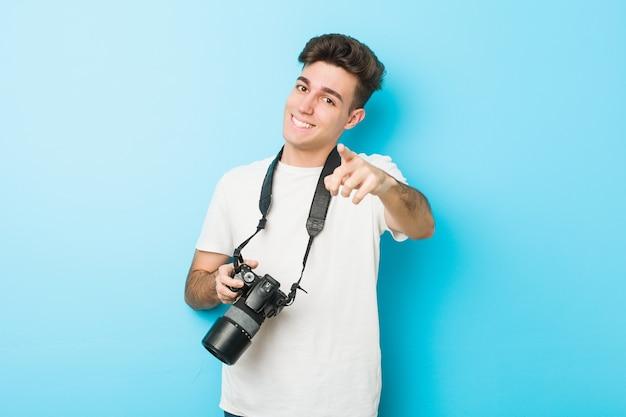 Uomo caucasico del giovane fotografo che tiene una macchina fotografica sorrisi allegri che indicano la parte anteriore.
