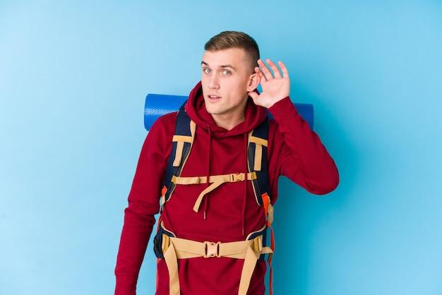 Uomo caucasico del giovane viaggiatore che prova ad ascoltare un gossip.