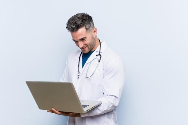 Uomo caucasico del medico con un computer portatile