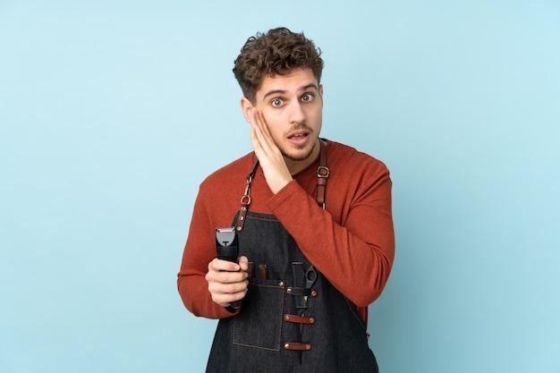 Uomo caucasico del parrucchiere sulla parete blu che bisbiglia qualcosa