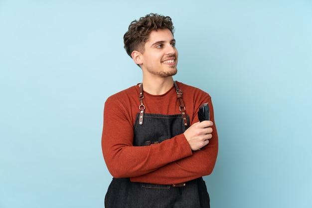 Uomo caucasico del parrucchiere sulla parete blu che guarda al lato