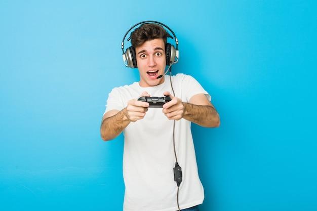 Uomo caucasico dell'adolescente che per mezzo delle cuffie e del controller di gioco