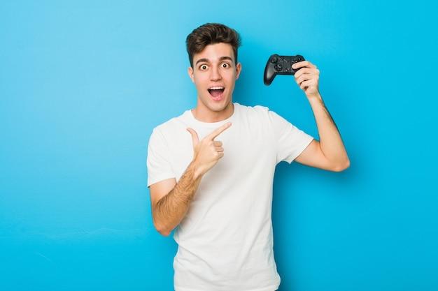 Uomo caucasico dell'adolescente che per mezzo di un controller di gioco