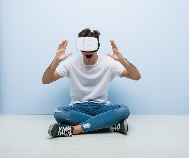 Uomo caucasico dell'adolescente che usando i vetri di una realtà virtuale che si siedono sul pavimento