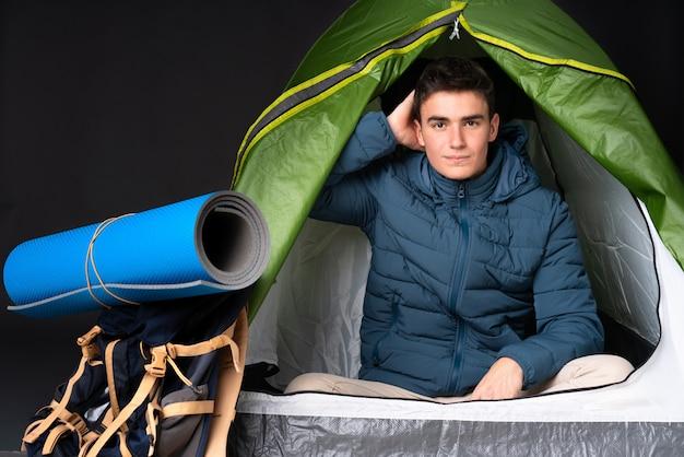 Uomo caucasico dell'adolescente dentro una tenda verde di campeggio isolata sul nero con un'espressione di frustrazione e di non comprensione