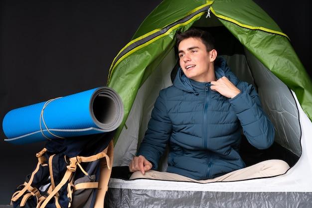 Uomo caucasico dell'adolescente dentro una tenda verde di campeggio isolata sul nero