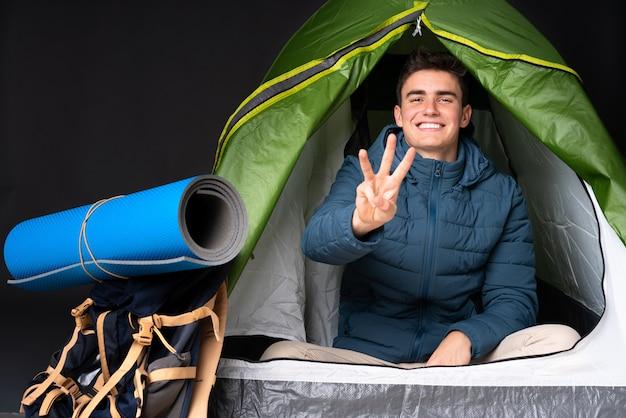 Uomo caucasico dell'adolescente dentro una tenda verde di campeggio sulla parete nera felice e contando tre con le dita