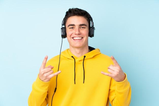 Uomo caucasico dell'adolescente isolato su musica d'ascolto del fondo porpora che fa gesto della roccia