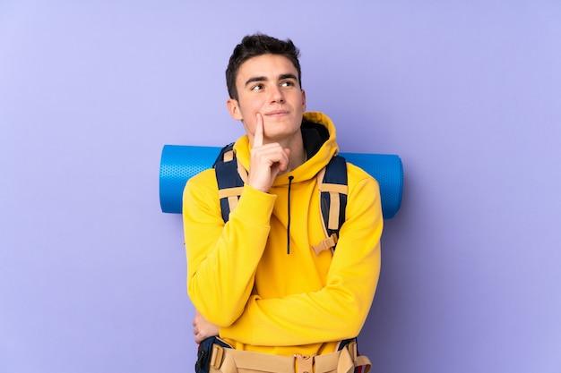 Uomo caucasico dell'alpinista dell'adolescente con un grande zaino isolato su viola che pensa un'idea
