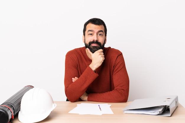 Uomo caucasico dell'architetto con la barba in un pensiero della tabella