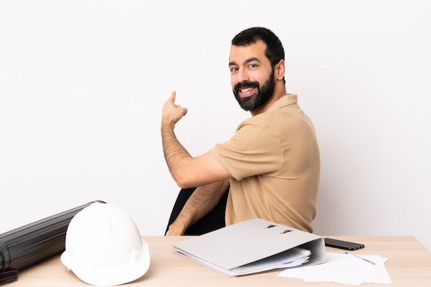 Uomo caucasico dell'architetto con la barba in una tabella che indica indietro.