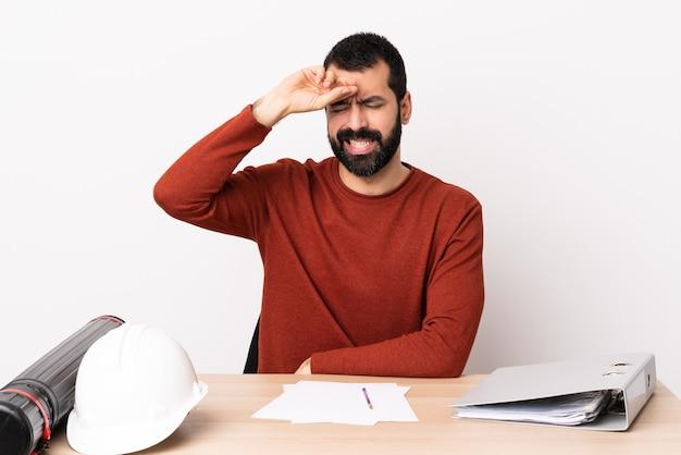 Uomo caucasico dell'architetto con la barba in una tabella con l'espressione stanca e ammalata