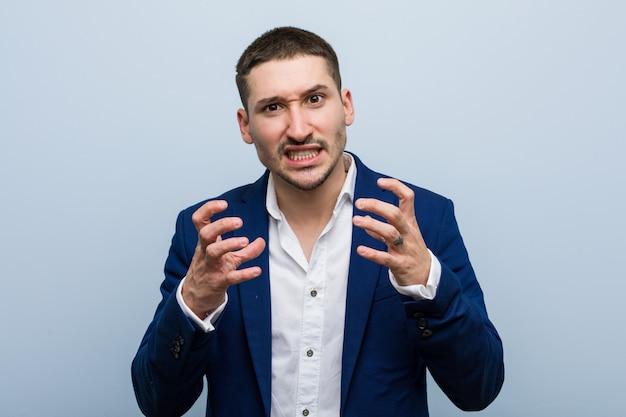 Uomo caucasico di affari giovane arrabbiato che grida con le mani tese.