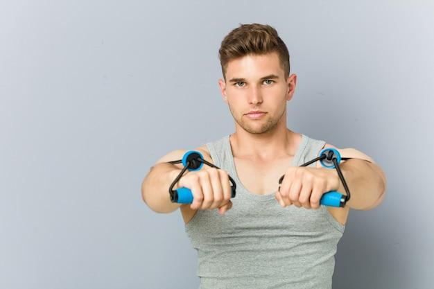 Uomo caucasico di giovane forma fisica che si esercita con un elastico.