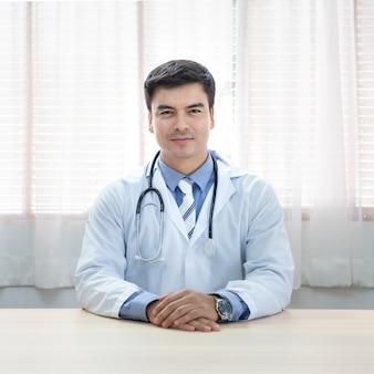 Uomo caucasico di giovane medico che si siede allo scrittorio al suo posto di lavoro e che sorride esaminando macchina fotografica. perfetto servizio medico in clinica. felice futuro della medicina e dell'assistenza sanitaria.