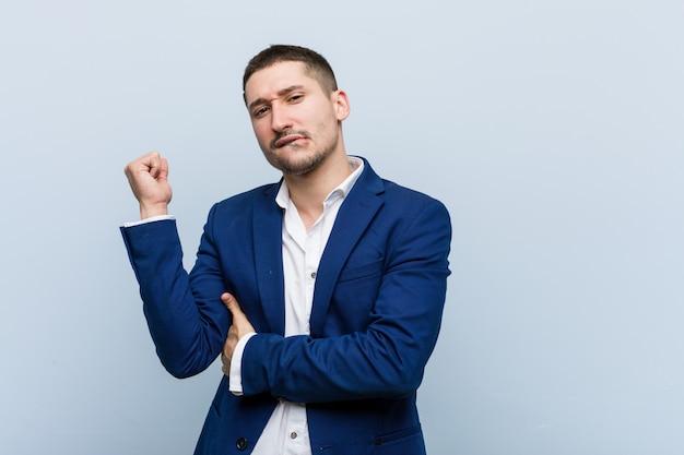 Uomo caucasico di giovani affari che tocca parte posteriore della testa, pensando e facendo una scelta.