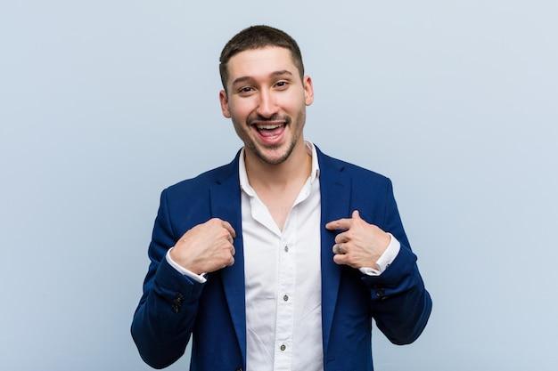 Uomo caucasico di giovani affari sorpreso indicando se stesso, sorridendo ampiamente.