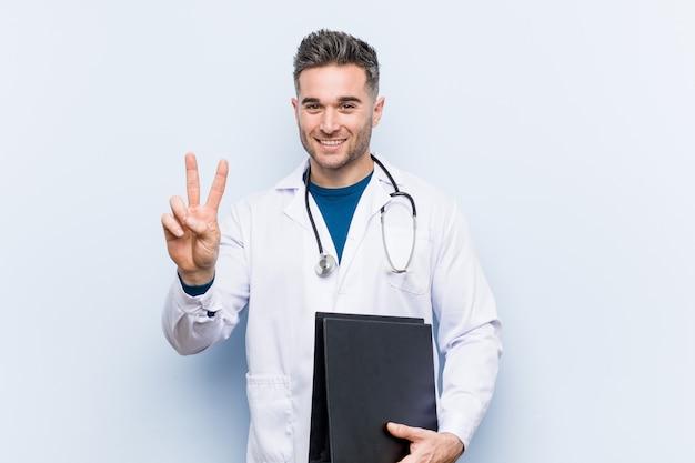 Uomo caucasico di medico che tiene una cartella che mostra numero due con le dita.