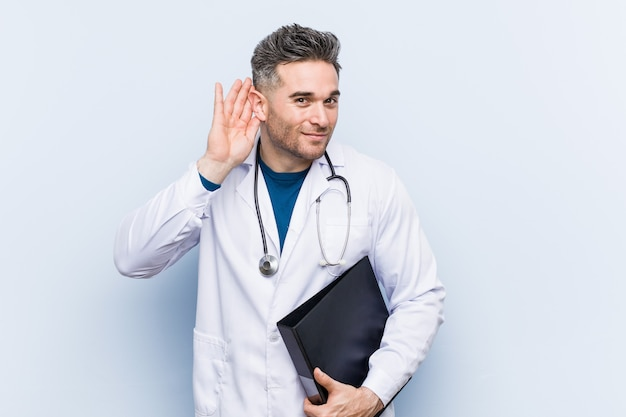 Uomo caucasico di medico che tiene una cartella che prova ad ascoltare un gossip.
