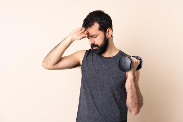 Uomo caucasico di sport con la barba che fa sollevamento pesi sopra la parete con l'espressione stanca e malata