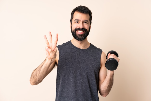 Uomo caucasico di sport con la barba che rende felice il sollevamento pesi sopra la parete e che conta tre con le dita