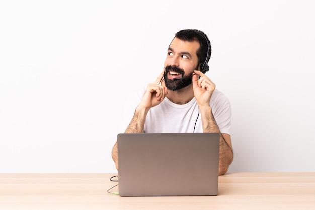 Uomo caucasico di telemarketer che lavora con una cuffia avricolare e con il computer portatile che pensa un'idea mentre osservando in su