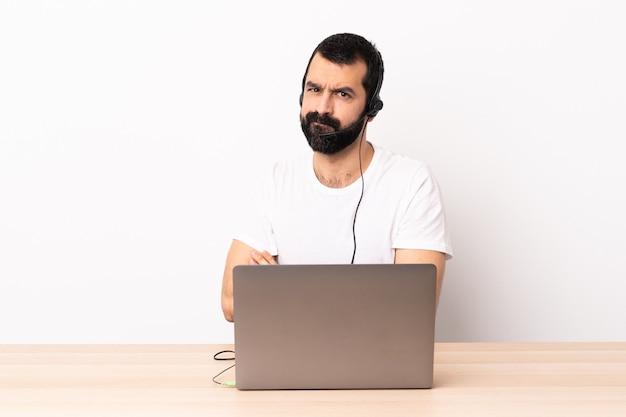 Uomo caucasico di telemarketer che lavora con una cuffia avricolare e con la sensibilità del computer portatile turbata.