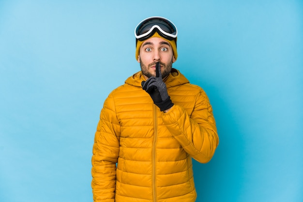 Uomo caucasico giovane sciatore isolato mantenendo un segreto o chiedendo silenzio.