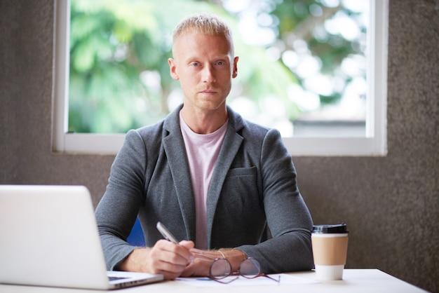 Uomo caucasico in giacca sportiva che si siede allo scrittorio in ufficio con il computer portatile e che esamina macchina fotografica