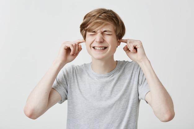 Uomo caucasico infastidito arrabbiato con capelli chiari stringe i denti vestito con una maglietta grigio chiaro che tappava le orecchie con le dita, irritato da un forte rumore. emozioni, sentimenti e reazioni umane. linguaggio del corpo