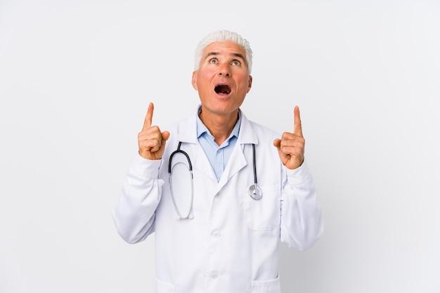 Uomo caucasico maturo di medico che indica parte superiore con la bocca aperta.