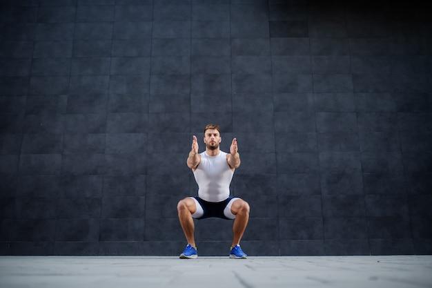 Uomo caucasico muscolare bello in breve e maglietta che fa esercizio accovacciato all'aperto. sullo sfondo è il muro grigio.