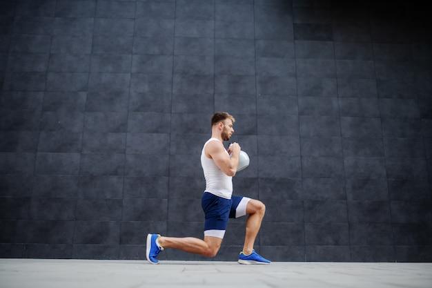 Uomo caucasico muscolare forte bello in pantaloncini e maglietta che fa affondi e che tiene la campana del bollitore. sullo sfondo è il muro grigio.