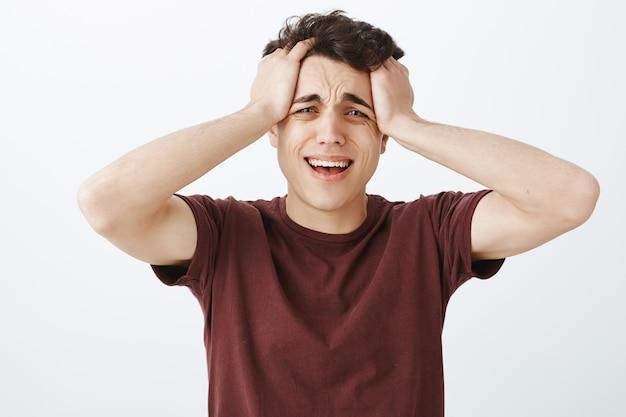 Uomo caucasico pianto disperato in maglietta rossa