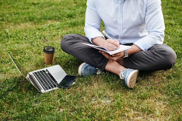Uomo caucasico ritagliata in abbigliamento d'affari, seduto sull'erba nel parco con le gambe incrociate e annotare le note in taccuino mentre si lavora al computer portatile