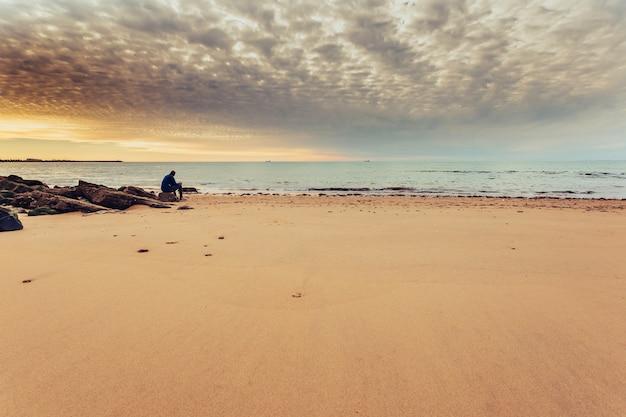 Uomo caucasico seduto da solo sulla riva del mare