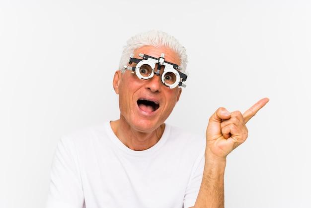 Uomo caucasico senior che indossa una struttura di prova dell'optometrista che sorride allegramente indicando con l'indice via.