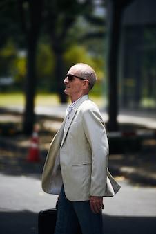 Uomo caucasico senior in occhiali da sole e giacca sportiva che camminano nel parco urbano
