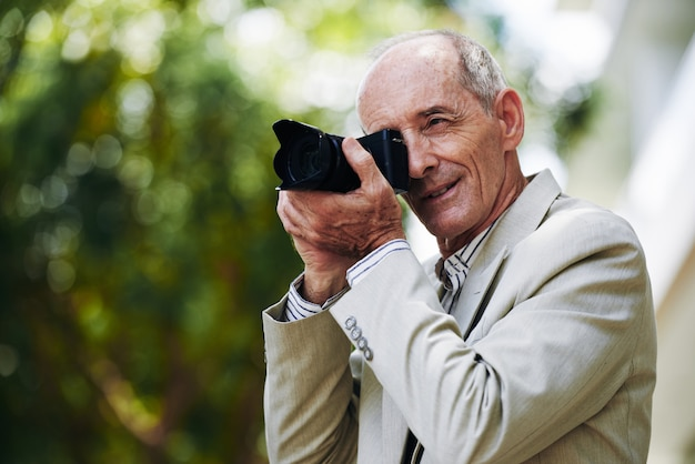 Uomo caucasico senior in vestito che prende le foto in via