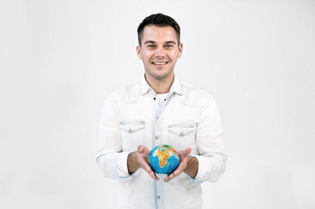 Uomo caucasico sorridente felice dei pantaloni a vita bassa in abbigliamento casual bianco che tiene poco globo della terra contro il fondo bianco isolato