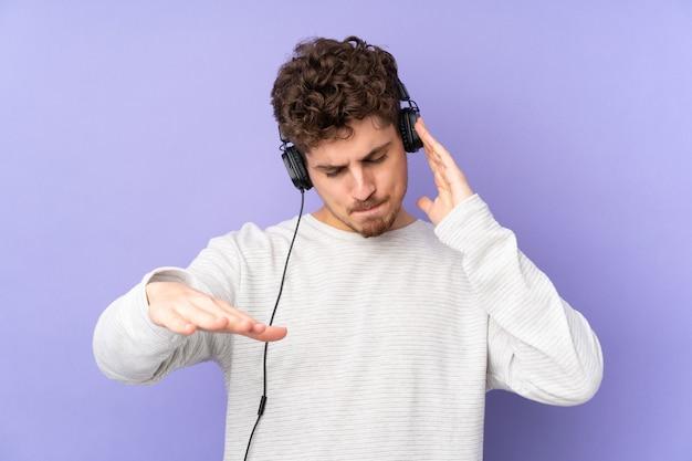 Uomo caucasico su musica e ballare d'ascolto della parete porpora